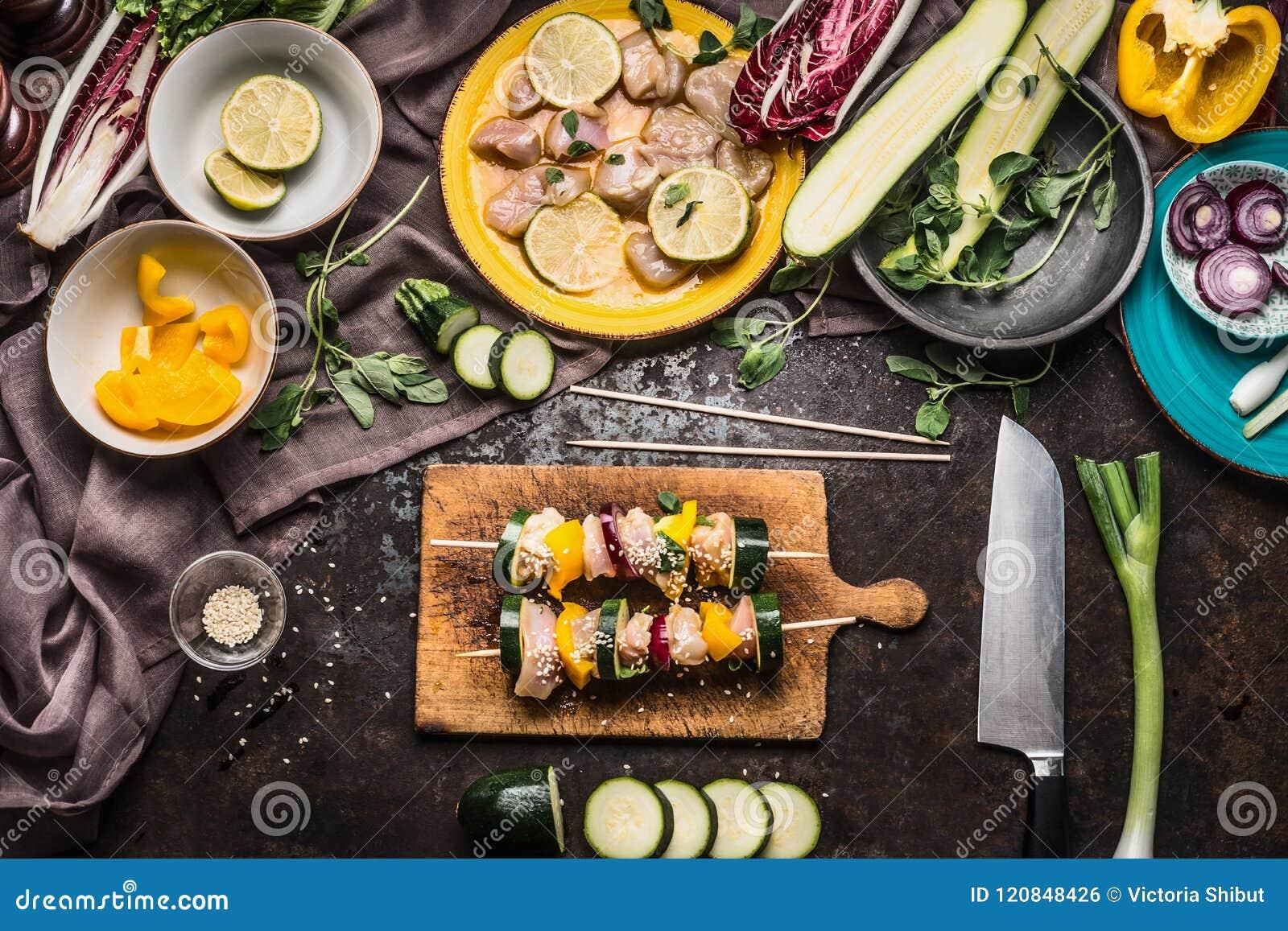 Preparação de vários espetos caseiros dos vegetais da carne da galinha para a grade ou o BBQ no fundo rústico com ingredientes