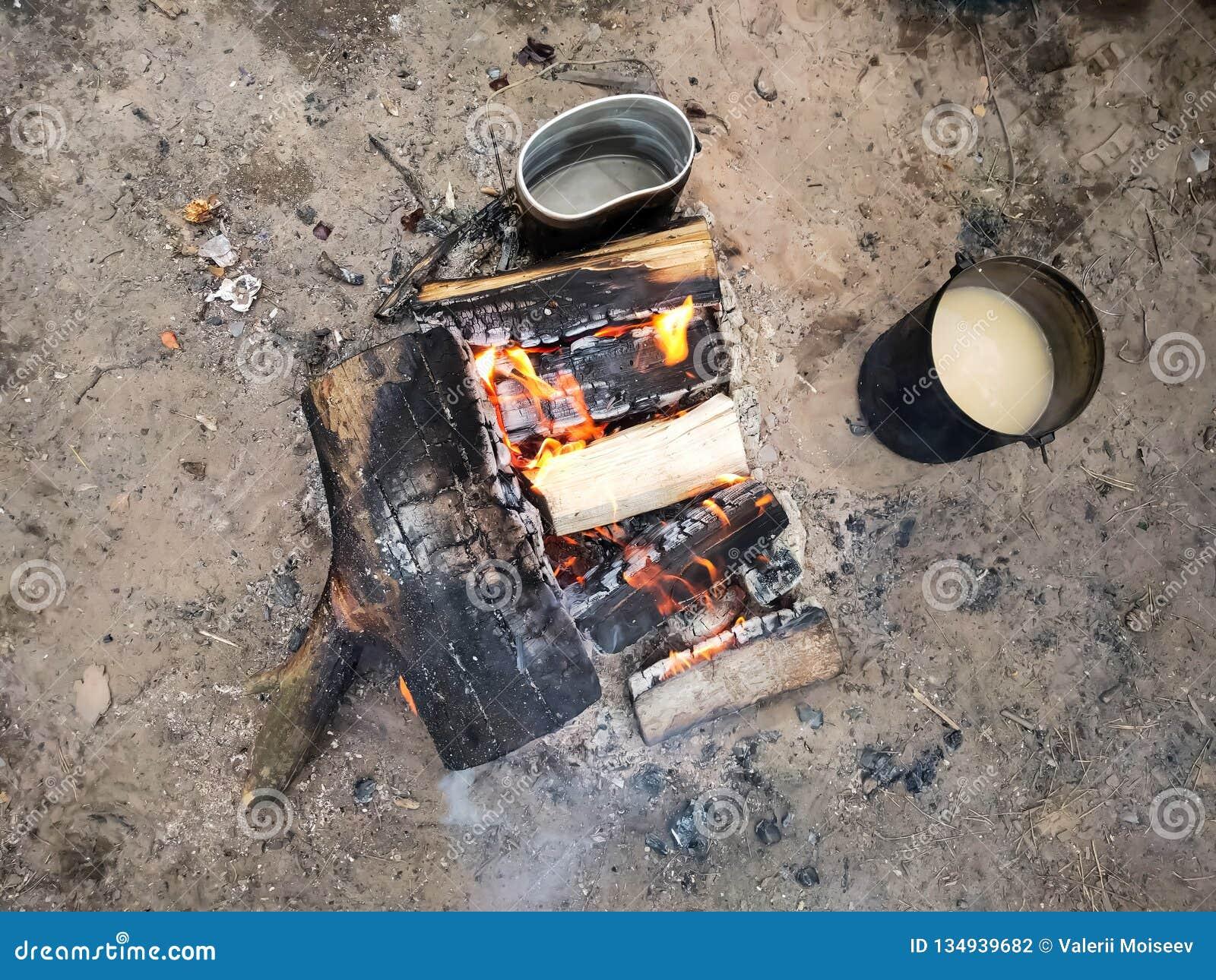 Preparação do alimento no fogo Jogador do turista no fogo, cozinhando na caminhada