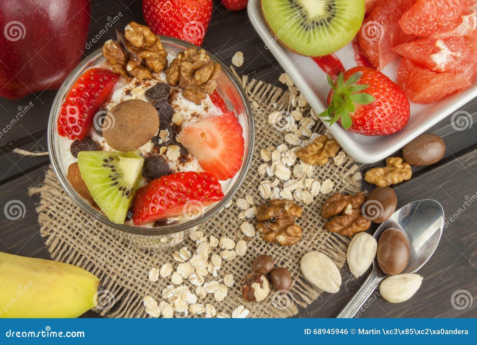 Preparación del desayuno sano para los niños Yogur con la harina de avena, la fruta, las nueces y el chocolate Harina de avena pa