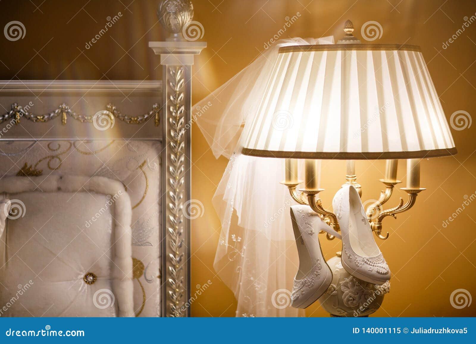 Preparaciones para la boda Zapatos blancos del vestido que se casa que cuelga en la lámpara
