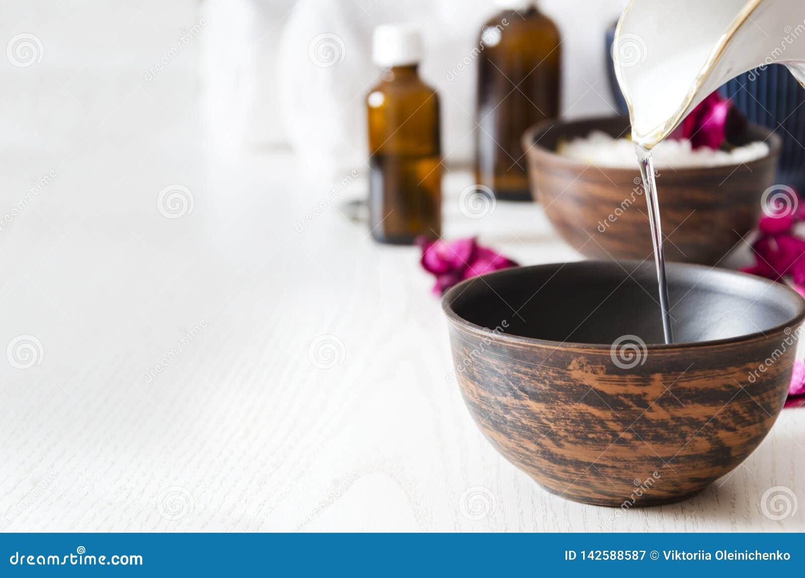 Preparandosi per il massaggio con olio cosmetico al salone della stazione termale, spazio della copia