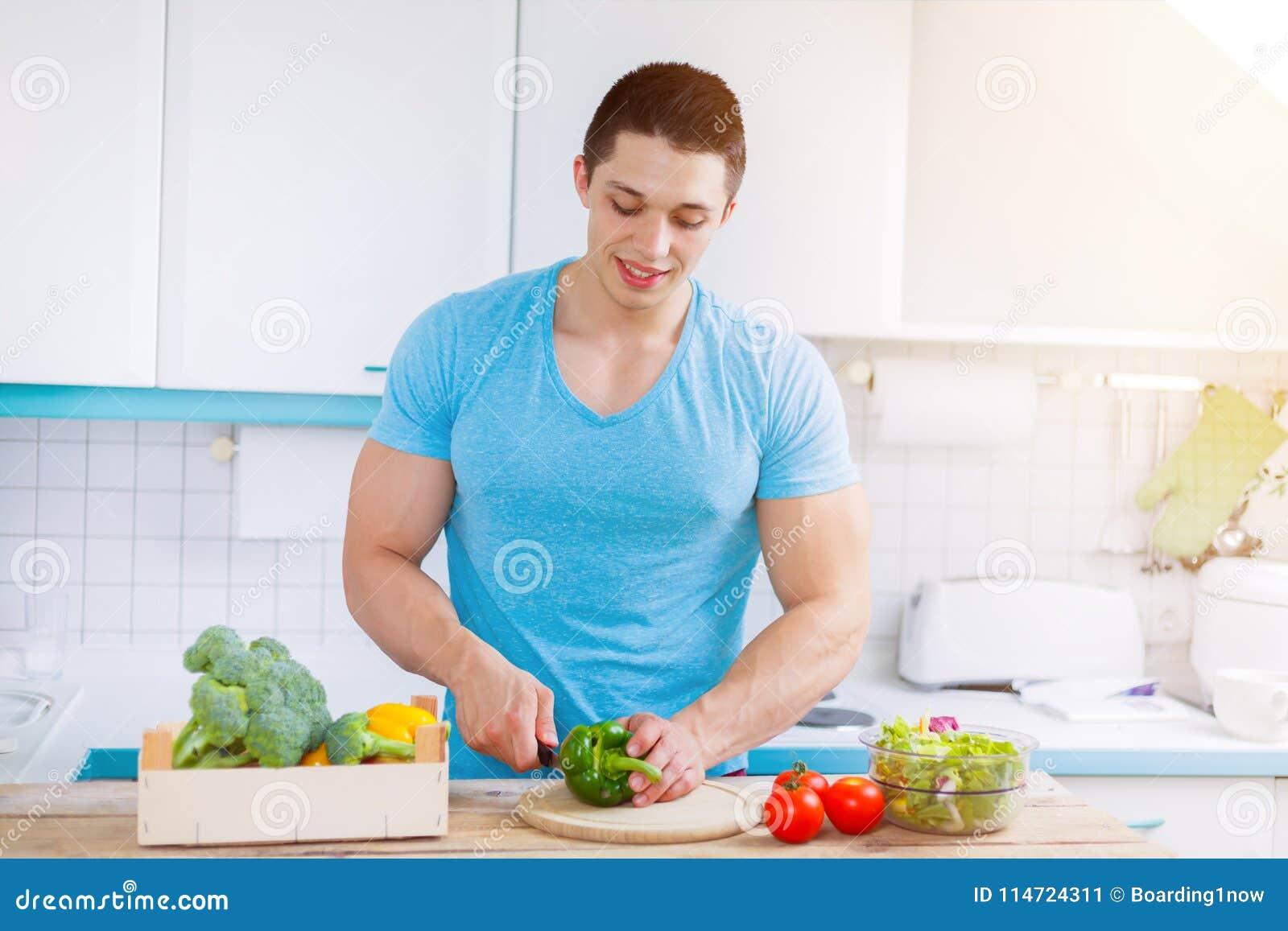 Preparar o alimento cortou o homem que novo dos vegetais a cozinha saudável da refeição come