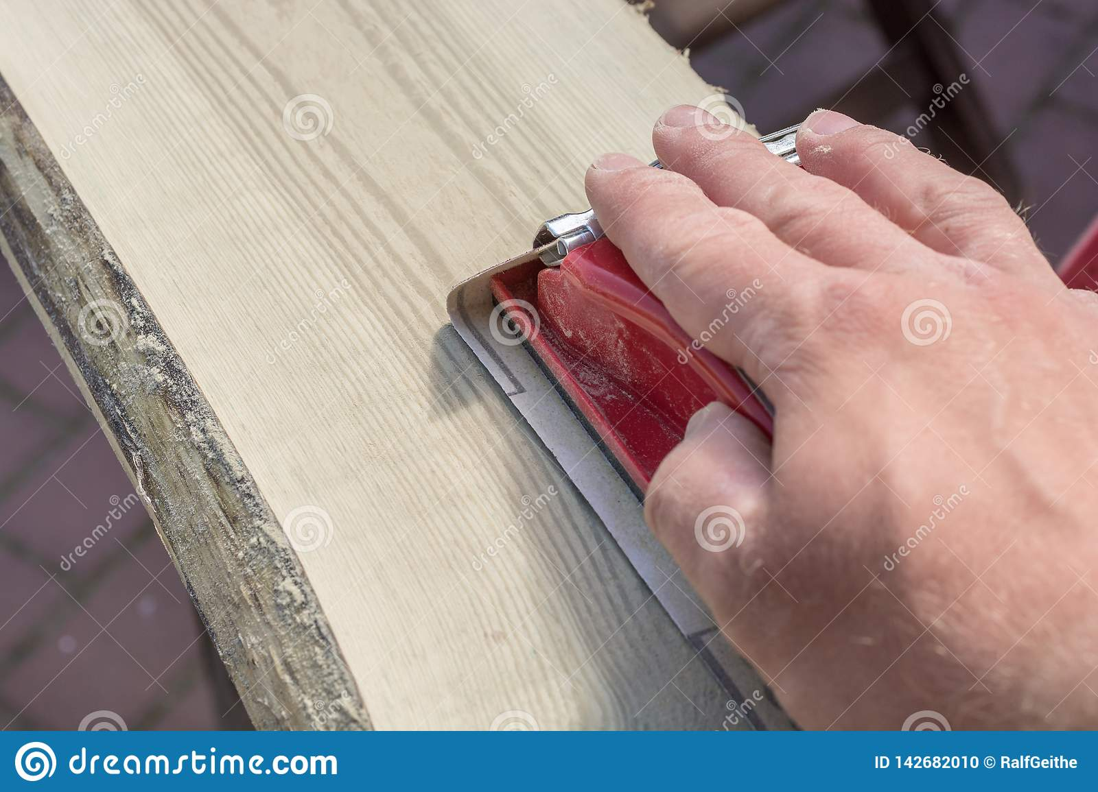 Preparation of an old wooden board by grinding with a hand sanding block