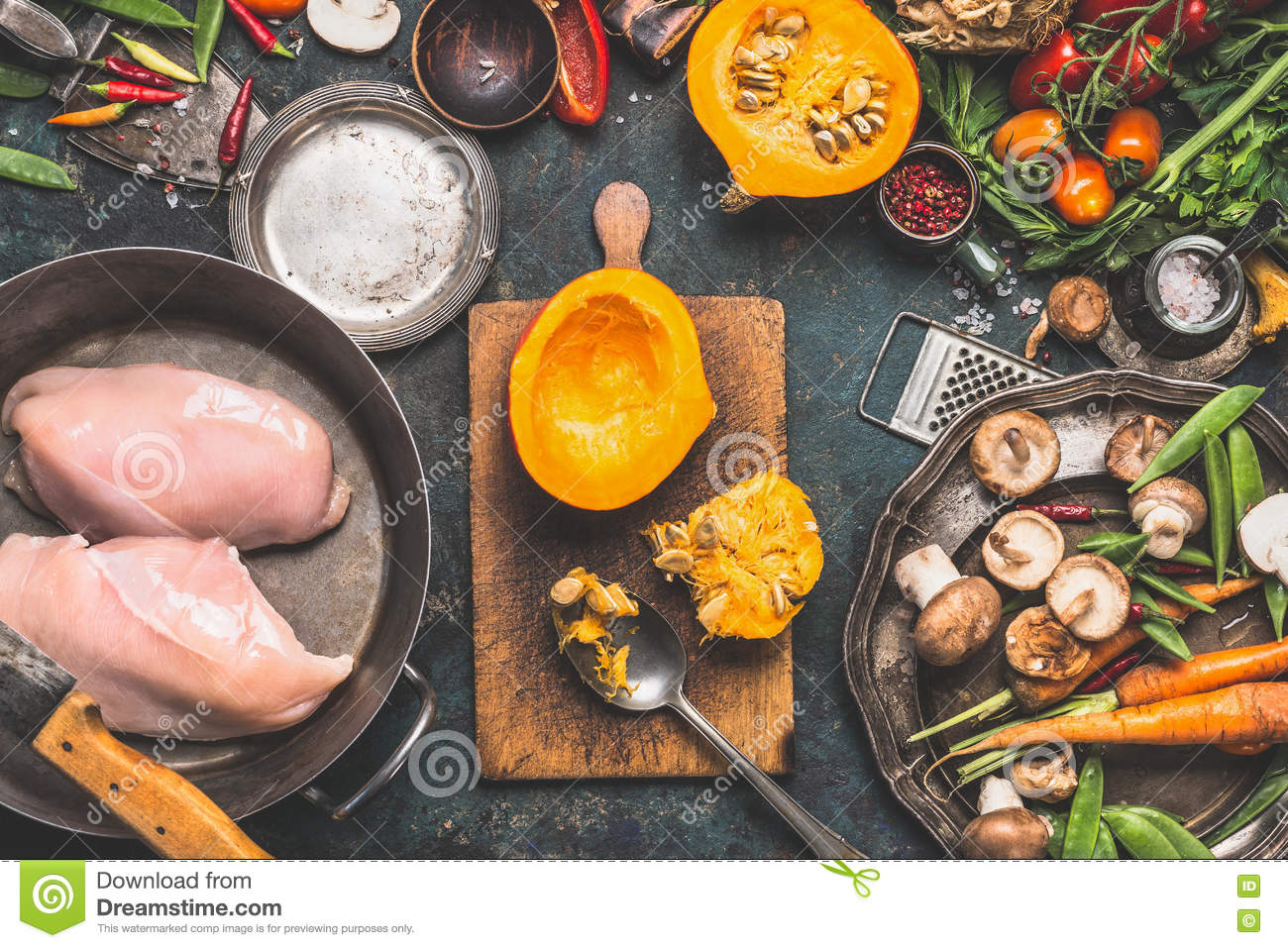 Preparation with Pumpkin , vegetables and mushrooms ingredients with Chicken breast in cooking pot, dark rustic background