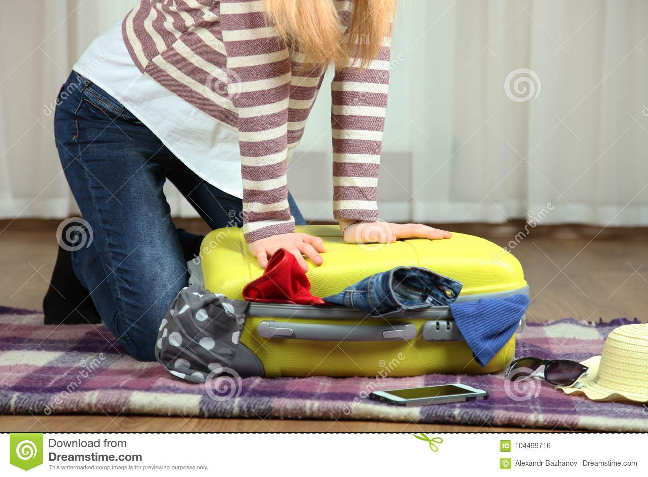 Girl closes the suitcase