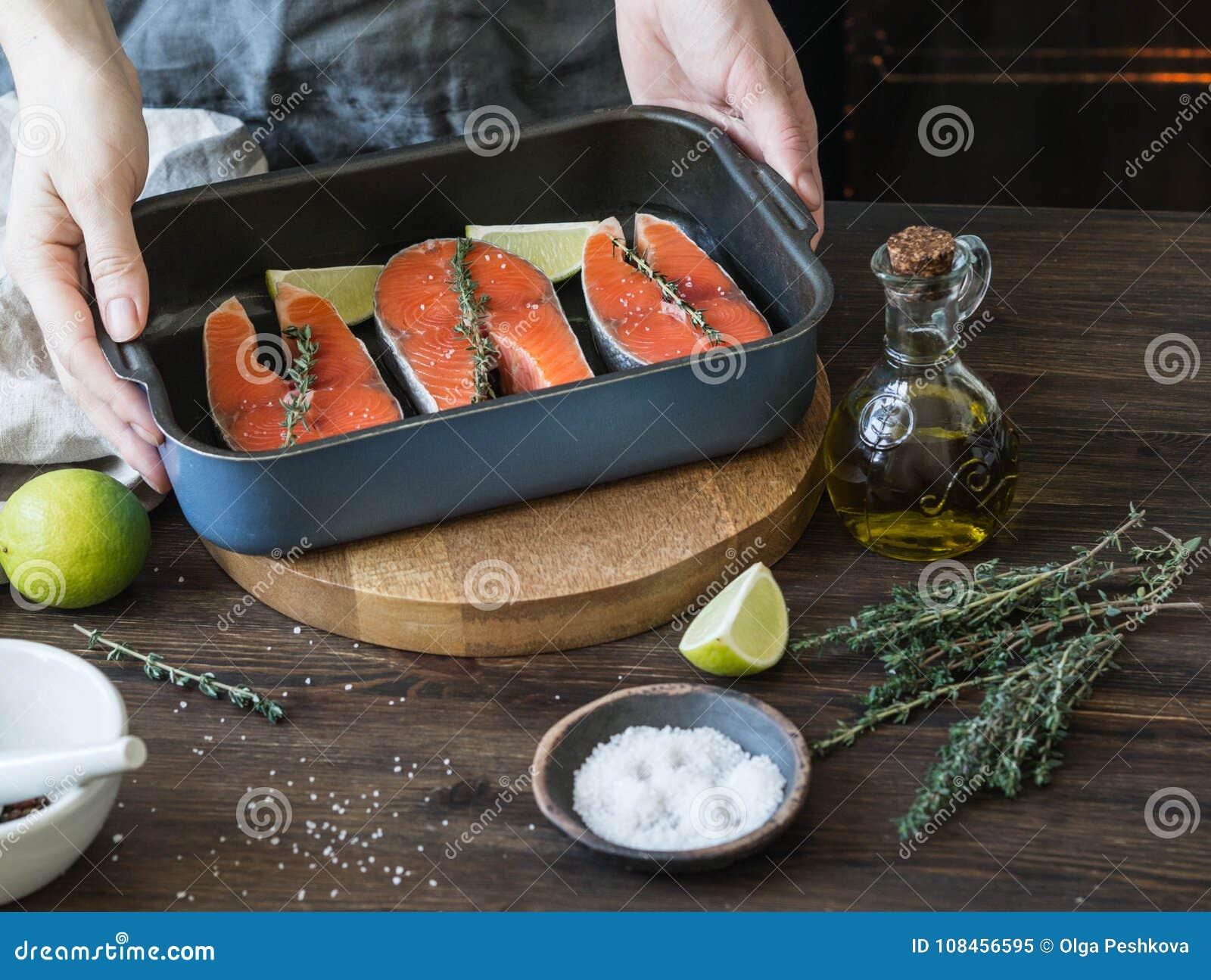 Preparazione del salmone Mani femminili con una fetta della calce Un vaso con le bistecche di color salmone crude
