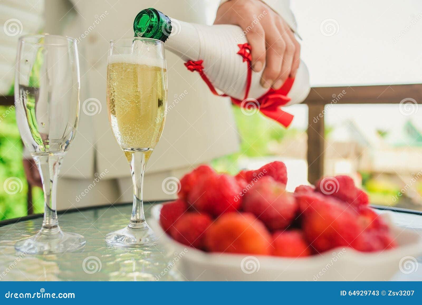 Prepare el champán de colada en un vidrio en el abierto