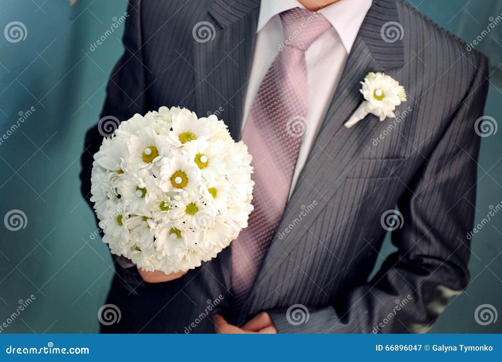 Prepare el ramo de la boda del control en su mano para la novia