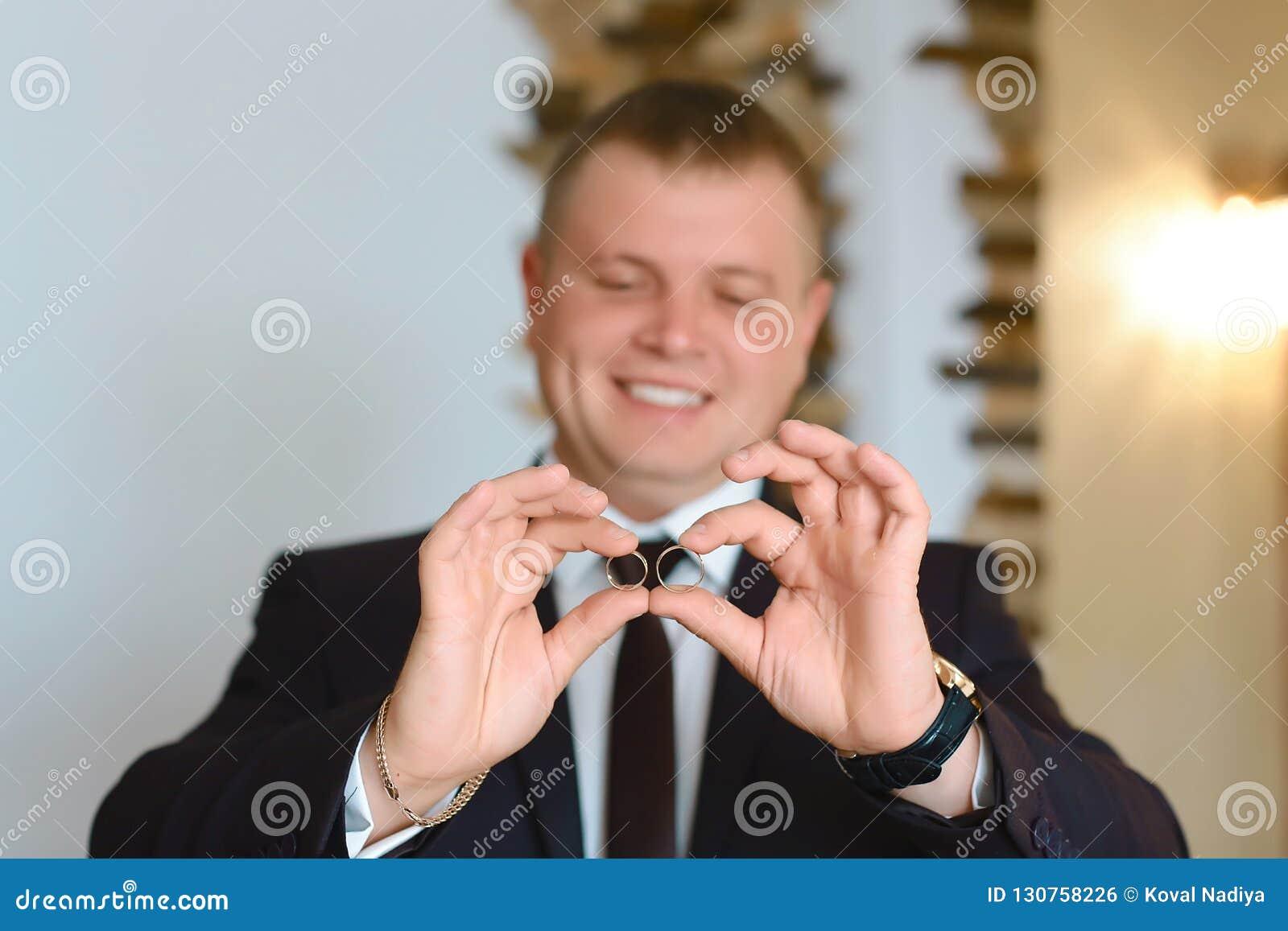 Prepare llevar a cabo los anillos de bodas en la palma en el traje, la mano del novio, anillo de bodas en mano del novio