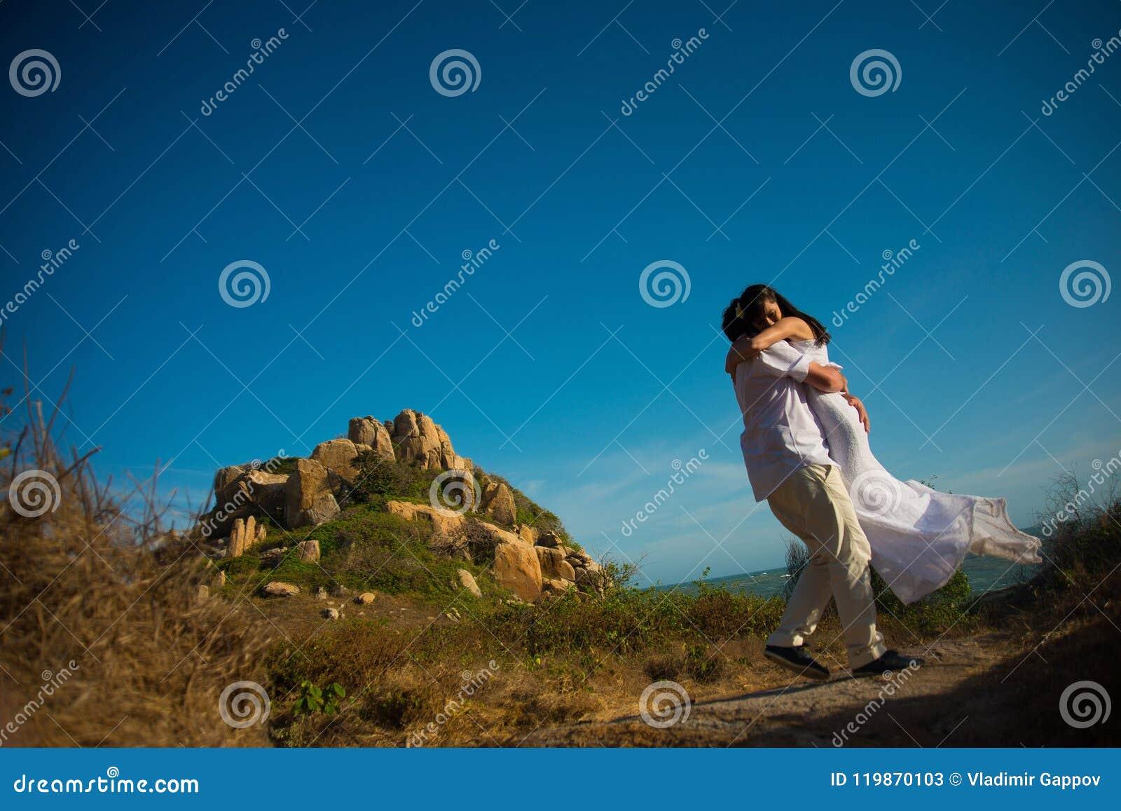 Prepare los círculos la novia en sus brazos contra las montañas y el cielo