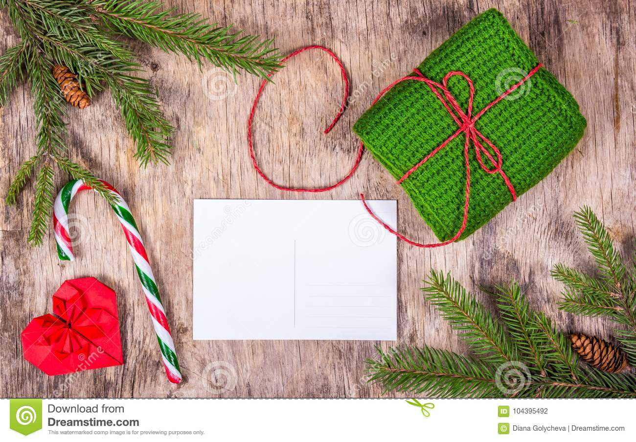 Preparing for Christmas. Blank postcard, ginger biscuit and knitted gift on old wooden board. Copy space