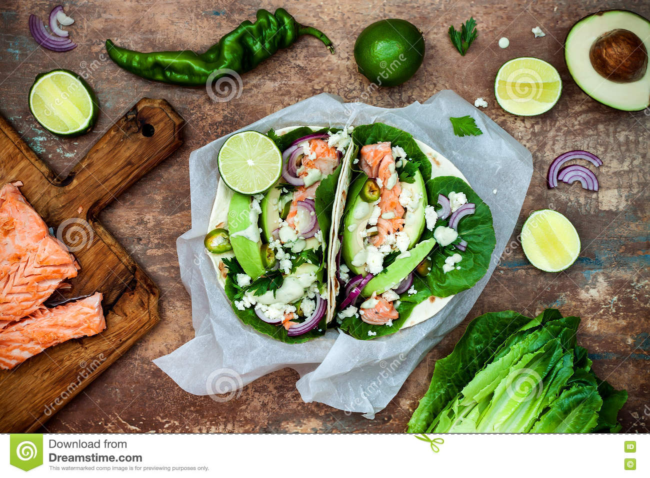 Preparing healthy lunch snacks. Fish tacos with grilled salmon, red onion, fresh salad leaves and avocado cilantro sauce