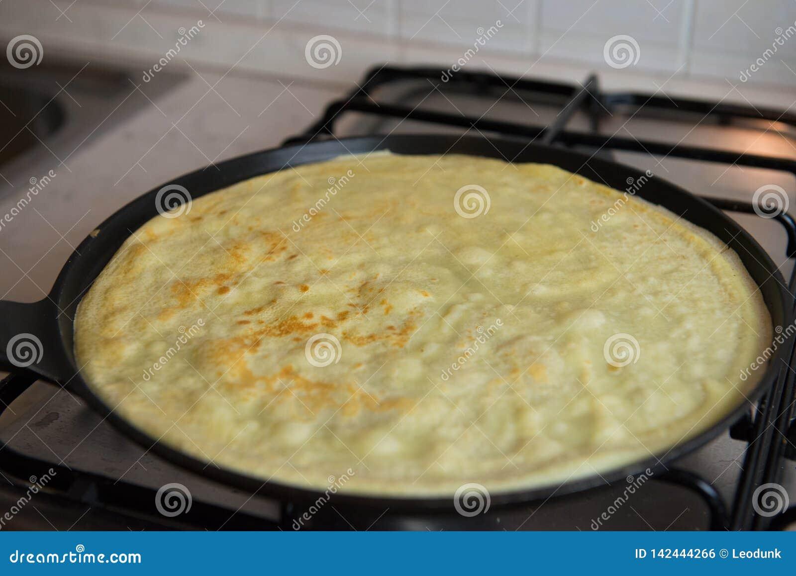 Preparing fresh homemade thin crepes pancakes