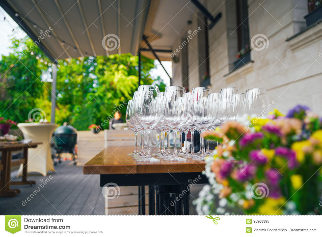 Preparing a terrace for the event. On the summer terrace there are tables with glasses. The concept of a party, wedding or birthda