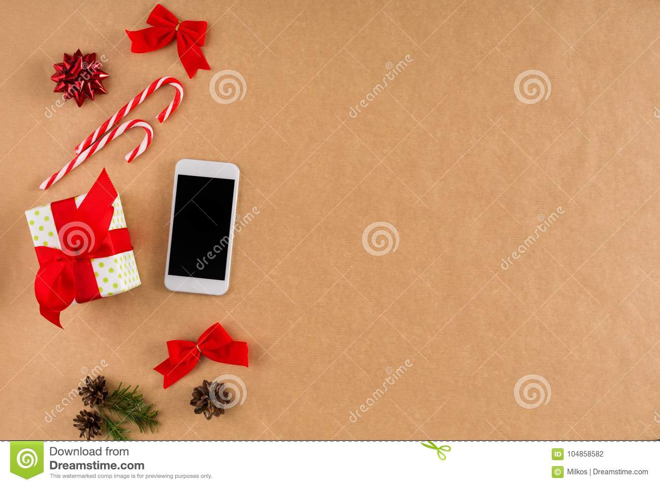 download phone and christmas decorations on craft paper background top view flat lay