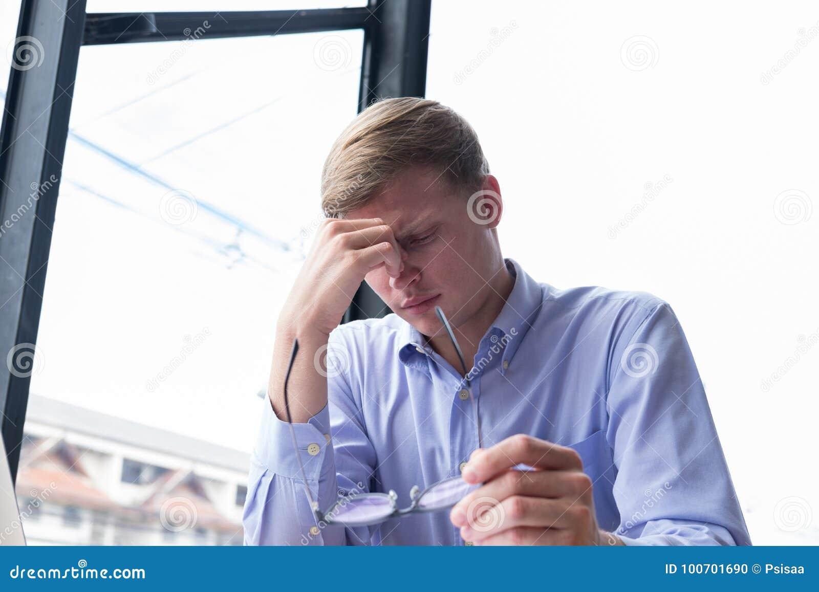 Presa stanca dell uomo d affari degli occhiali massag stressante del giovane