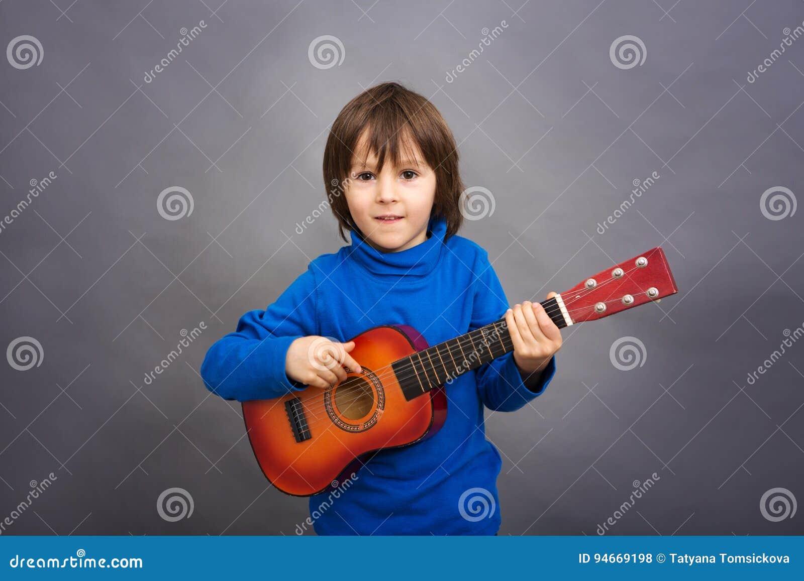 Preschool dziecko, bawić się małą gitarę, wizerunek