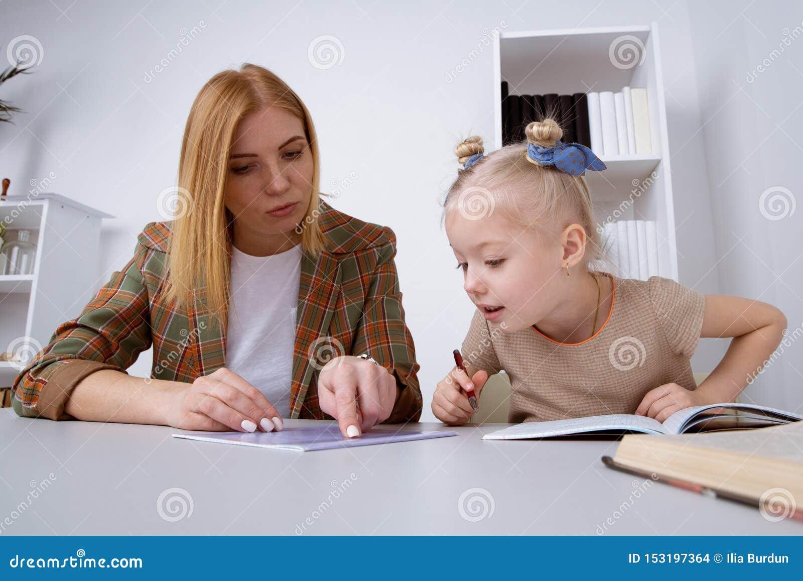 Preschool dziewczyna pisze zadaniu z jej matką przy biurkiem