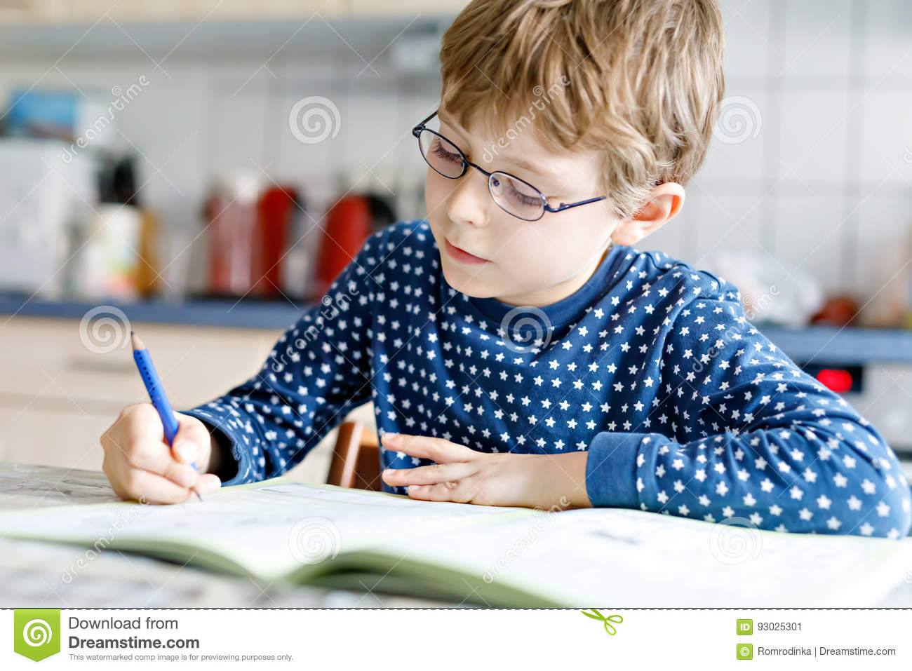 Preschool kid boy at home making homework writing letters with colorful pens