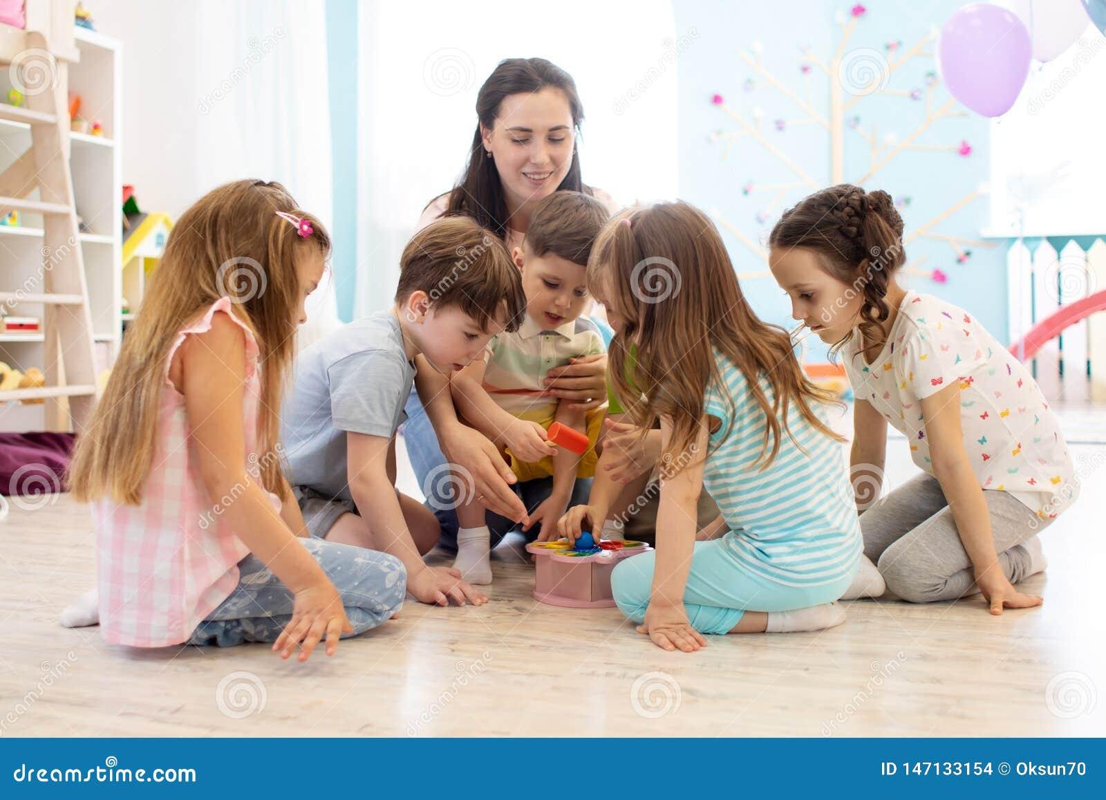 Preschool nauczyciel bawić się z grupą dzieciaki siedzi na podłodze przy dziecinem