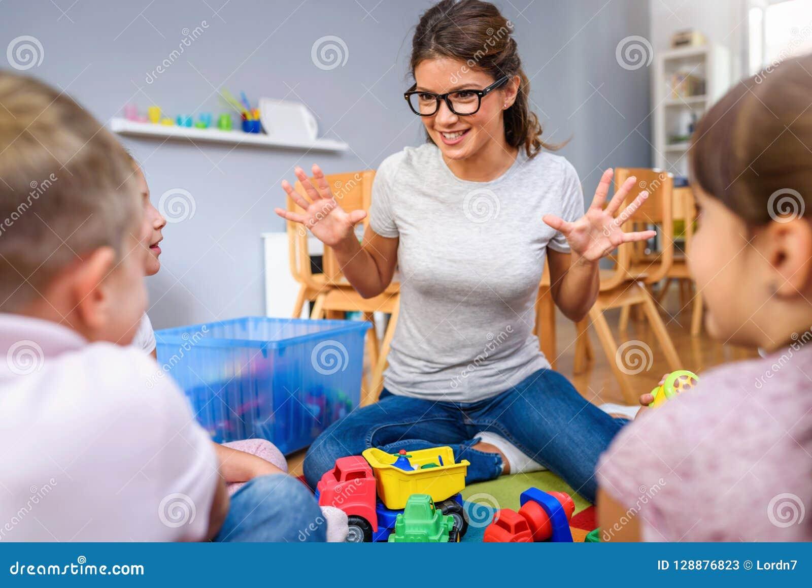 Preschool nauczyciel opowiada grupa dzieci siedzi na podłoga przy dziecinem