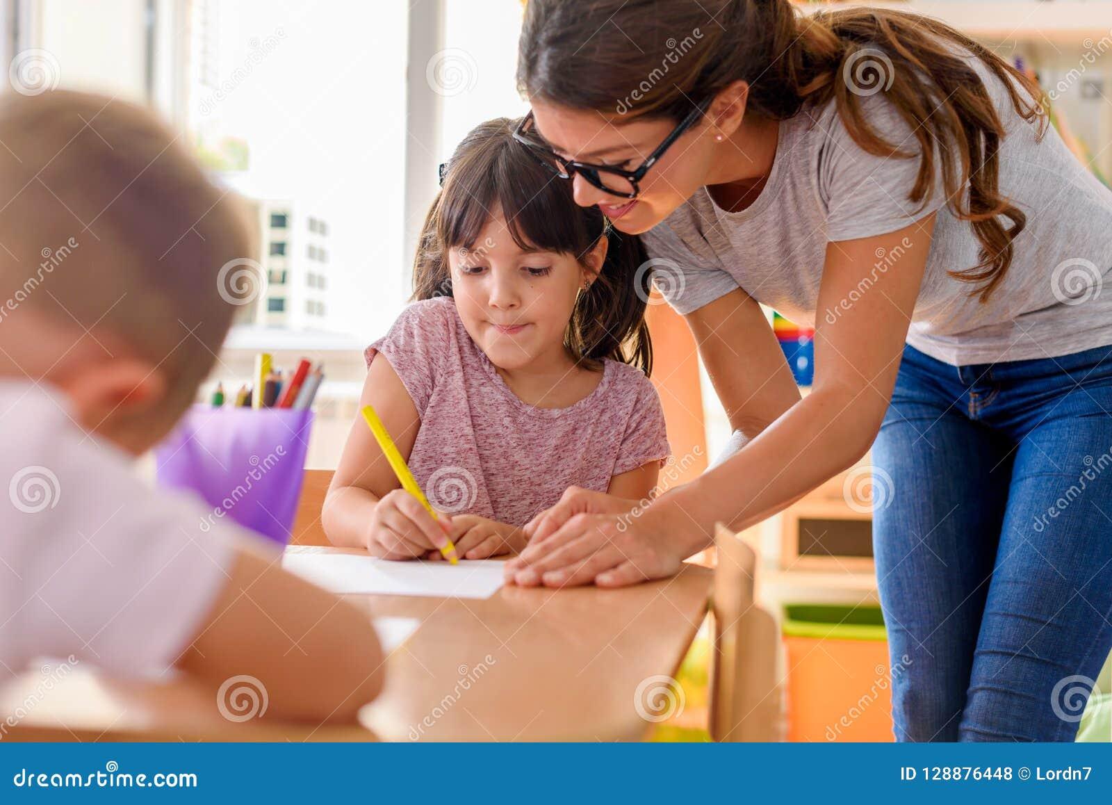 Preschool nauczyciel patrzeje mądrze dziecka przy dziecinem