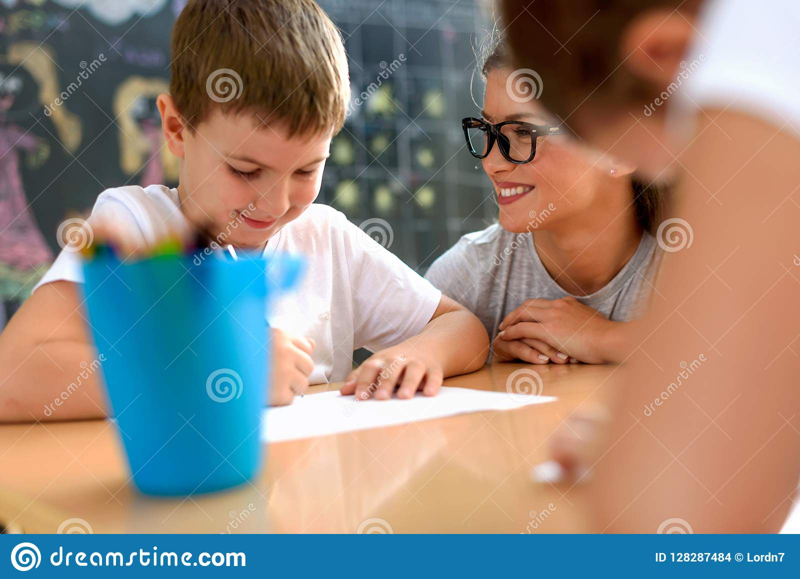 Preschool nauczyciel patrzeje mądrze uśmiechniętej chłopiec przy dziecinem