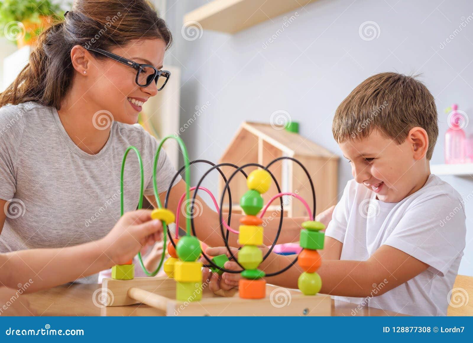 Preschool nauczyciel z dziećmi bawić się z kolorowymi dydaktycznymi zabawkami przy dziecinem