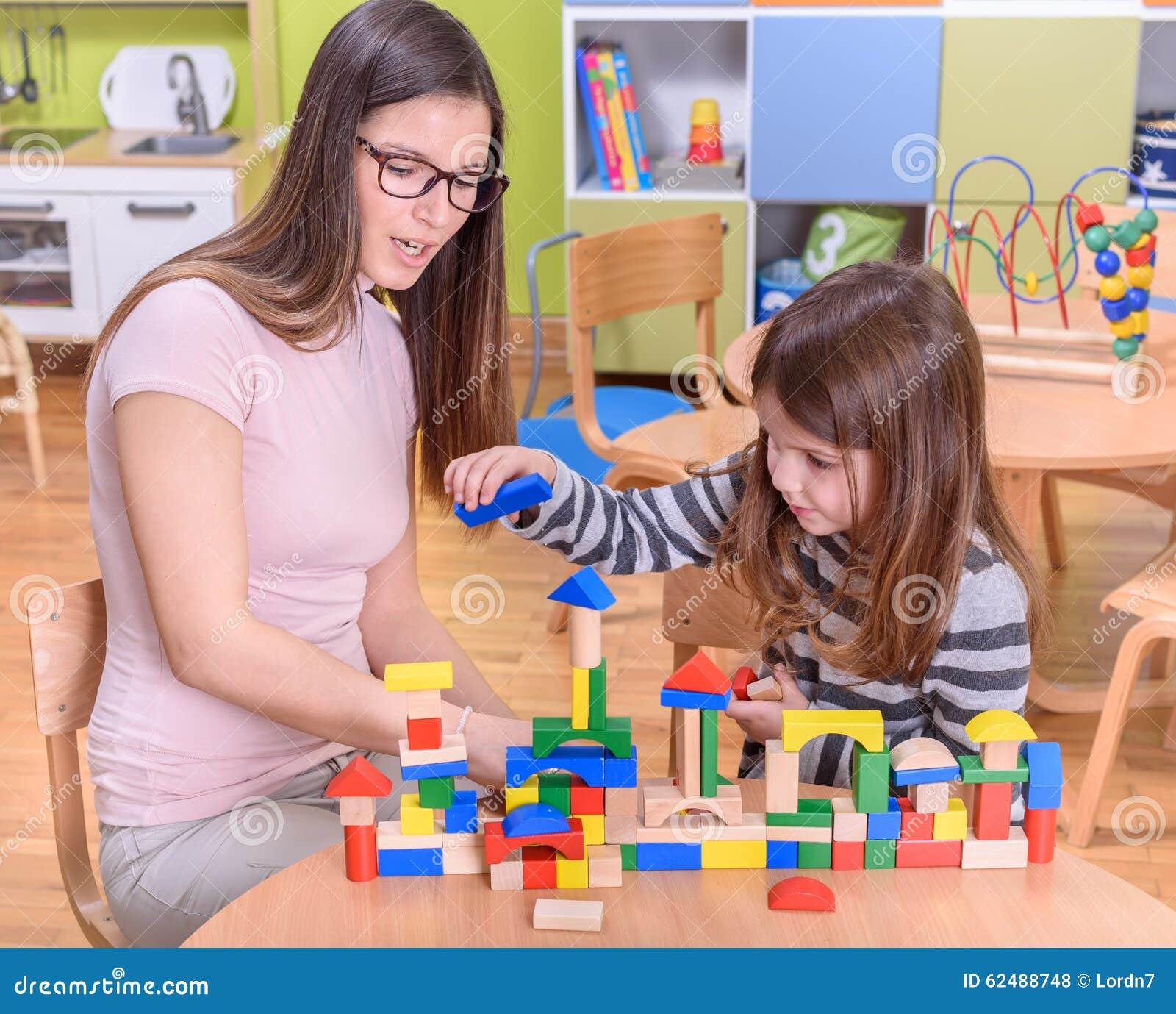 Toys For A Preschool Classroom : Preschool teacher helps cute girl to build toy castle