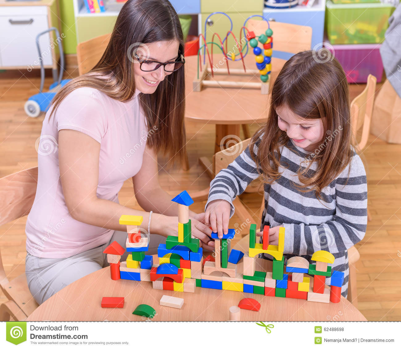 Preschool Teacher And Kid Building Castle Stock Photo