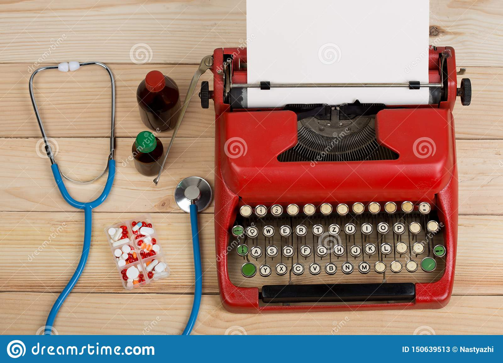 Prescription medicine or medical diagnosis - doctor workplace with stethoscope, pills, typewriter with blank paper on wooden table