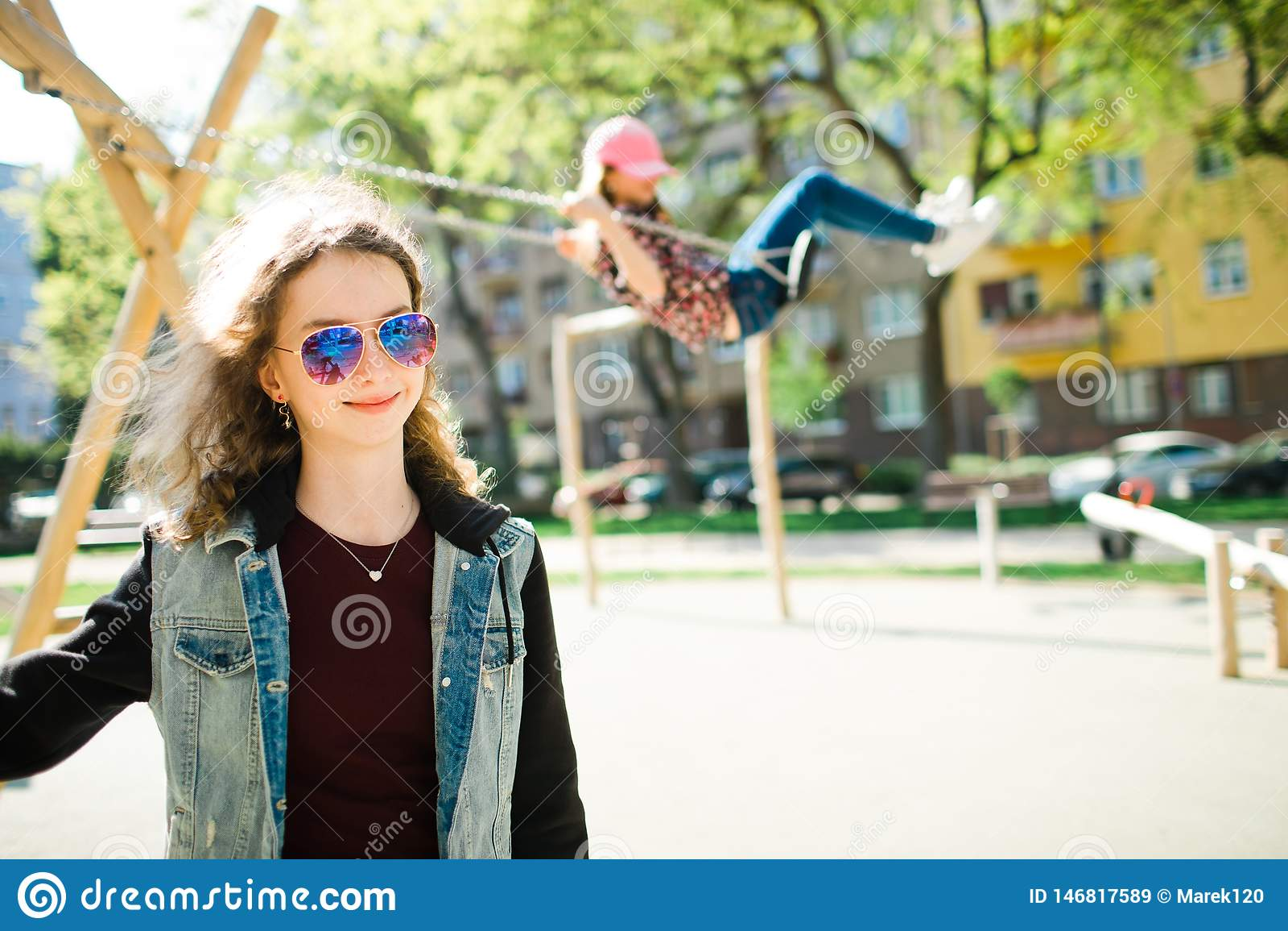 Presentación adolescente y niño de la muchacha de la edad en el casquillo rosado que balancea en patio en fondo