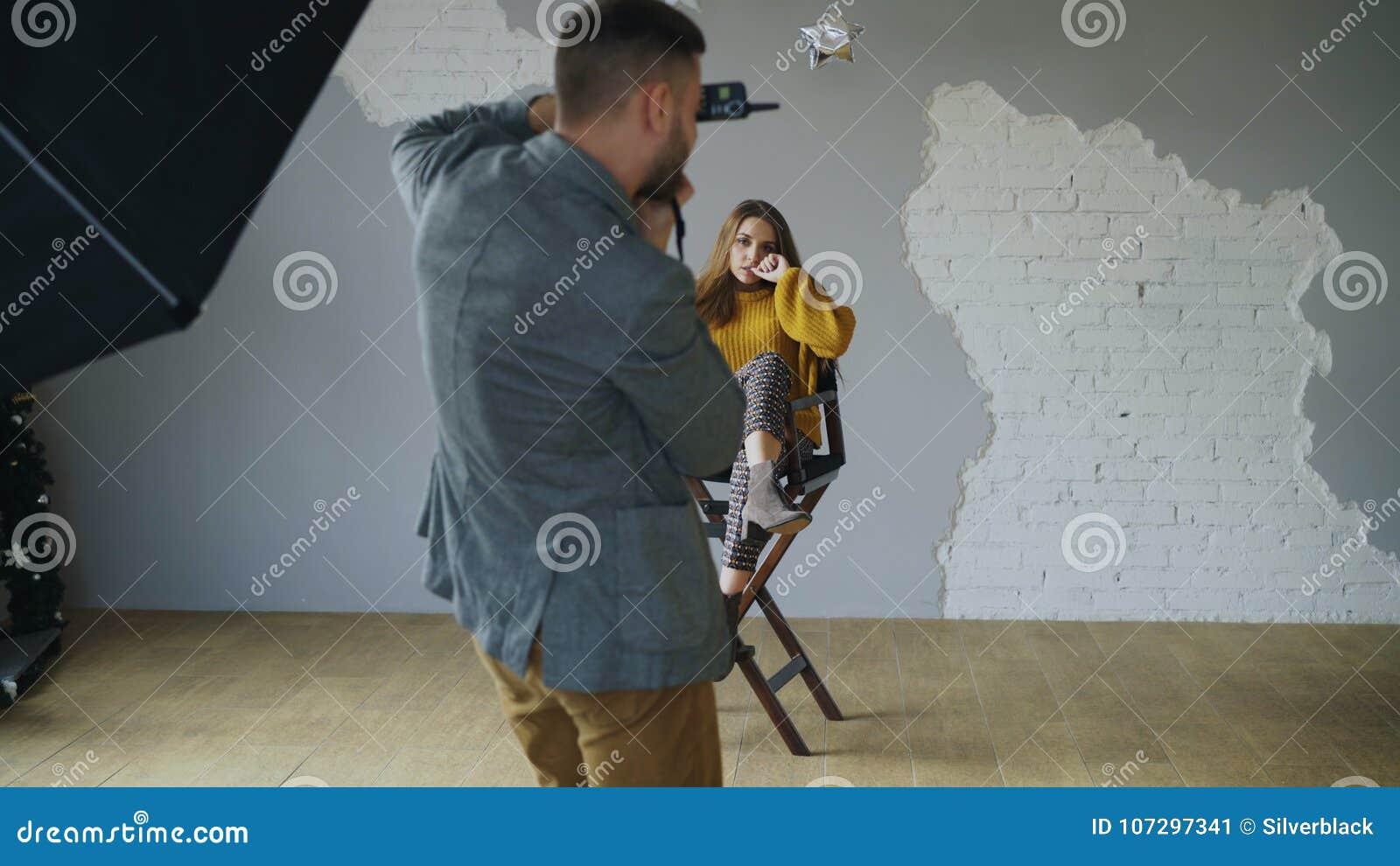 Presentación modelo de la mujer hermosa joven para el fotógrafo mientras que él está tirando con una cámara digital en estudio de