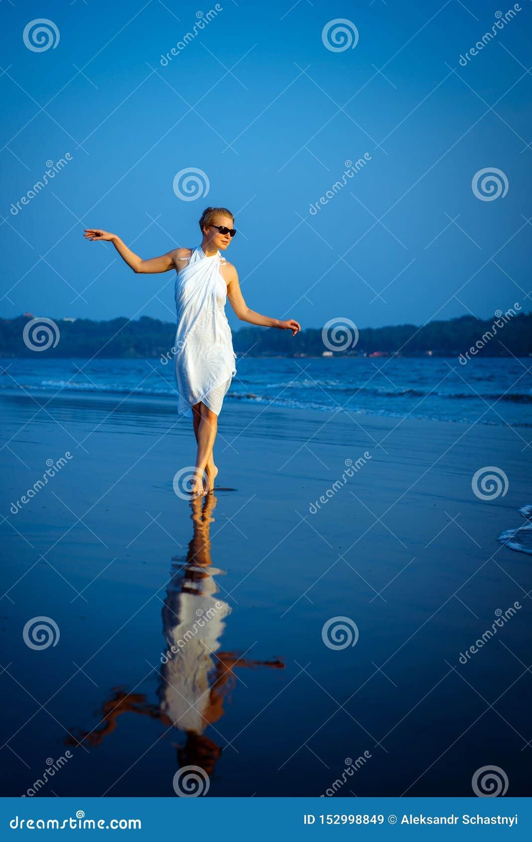 Presentación rubia hermosa y atractiva feliz joven contra el mar azul en el vestido y las gafas de sol blancos Muchacha elegante