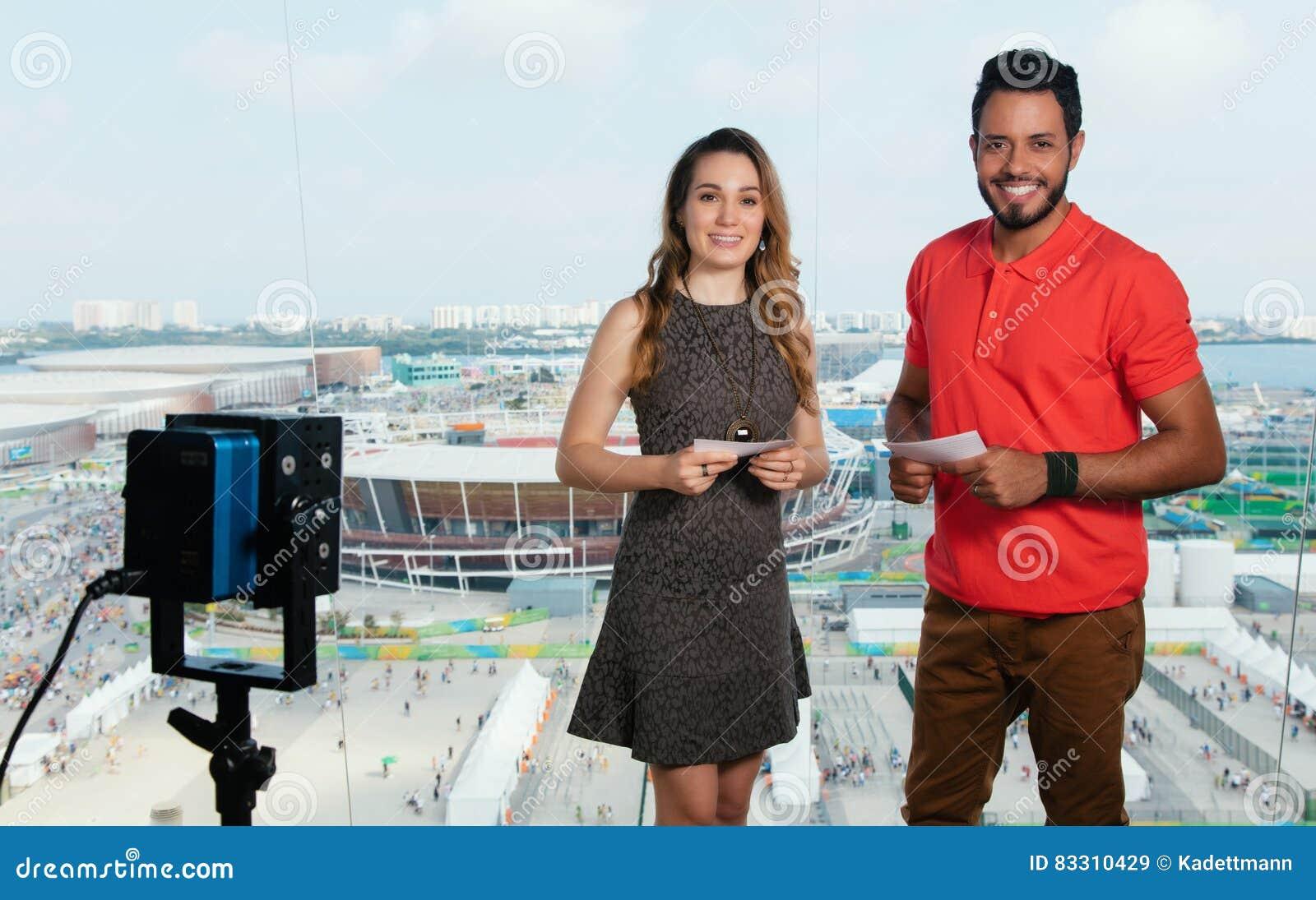 Presentador femenino caucásico y hombre latino en el estudio de la TV