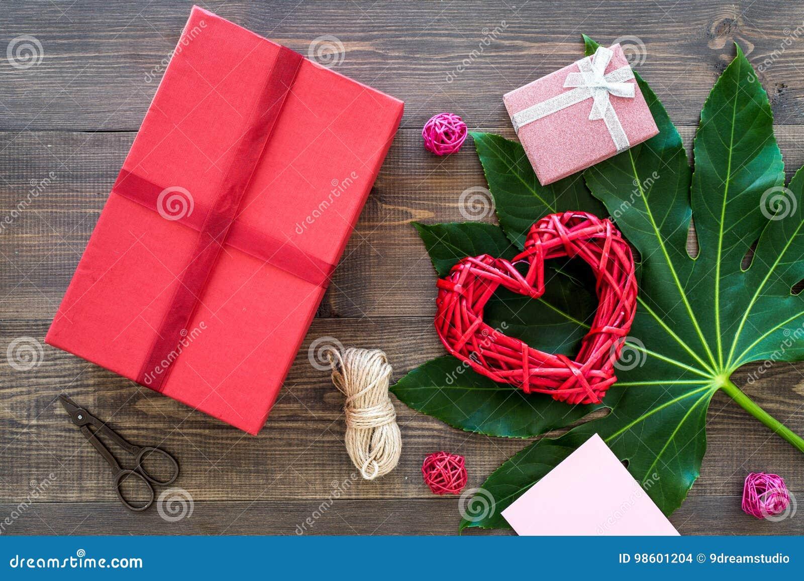 Presente de empacotamento Caixa de presente vermelha, sciccors, cabo fino na opinião superior do fundo de madeira escuro