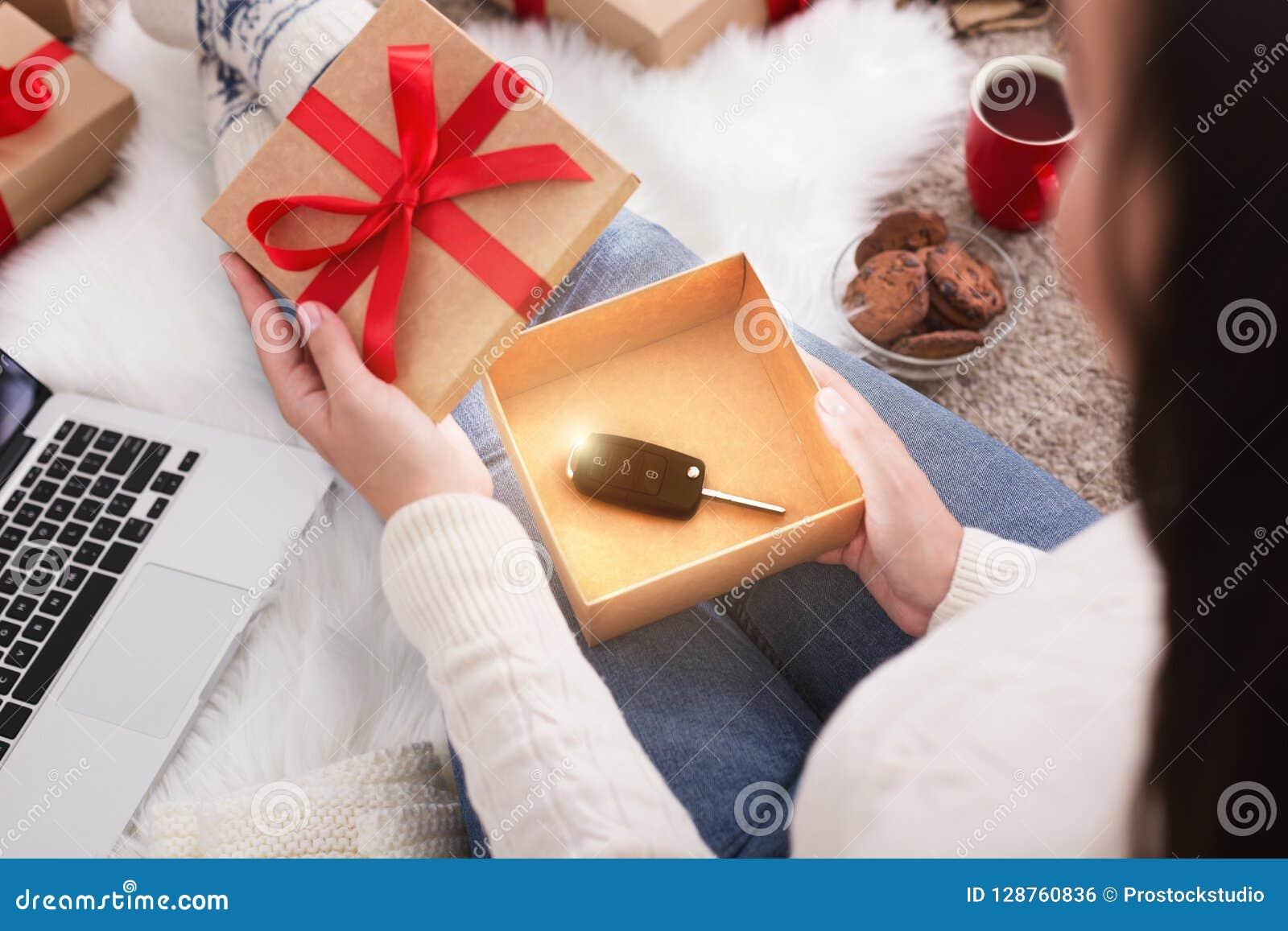 Presente e azevinho Presente do Natal da abertura da mulher com chave do carro
