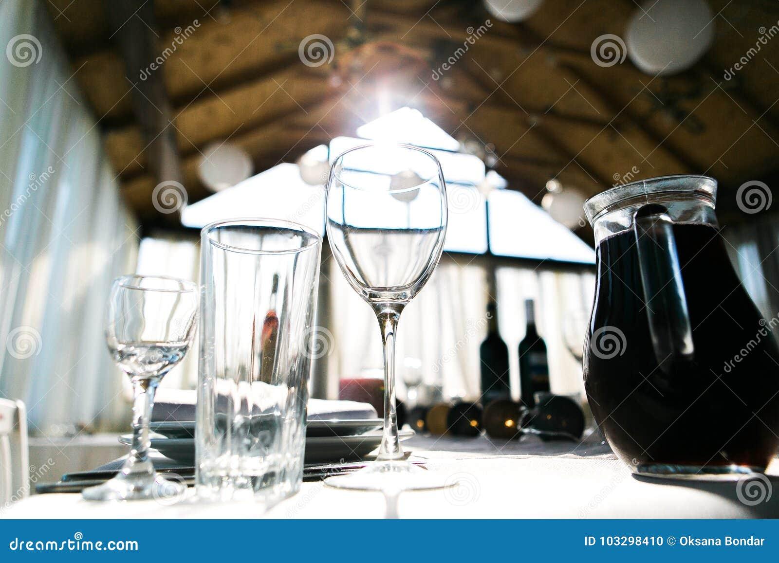 Presente el ajuste para la cena en restaurante, servido casandose la tabla con la decoración como las velas, copas de vino, linte