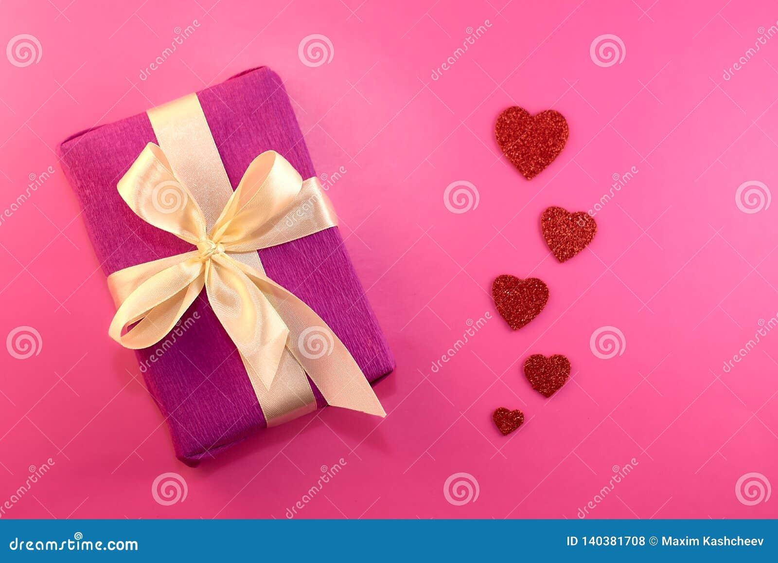 Presente ou caixa de presente, coração do papel e confetes na opinião superior do fundo do rosa Cartão do dia dos Valentim estilo