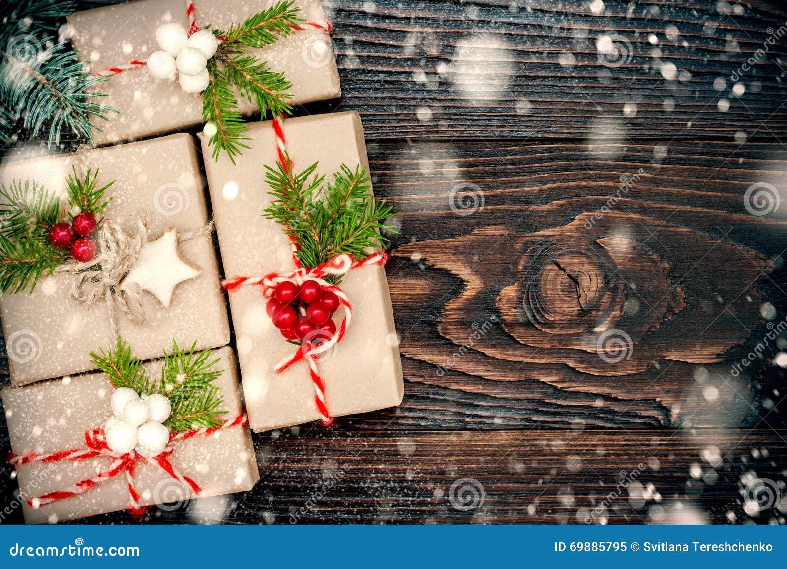 Presentes de Natal em umas caixas em um fundo de madeira com espaço da cópia Queda de neve tirada