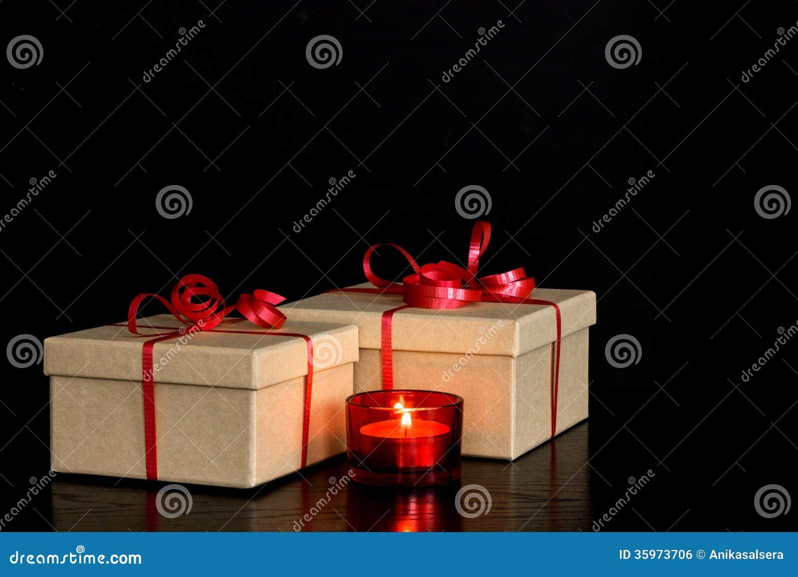 Presentes elegantes y luz de una vela roja