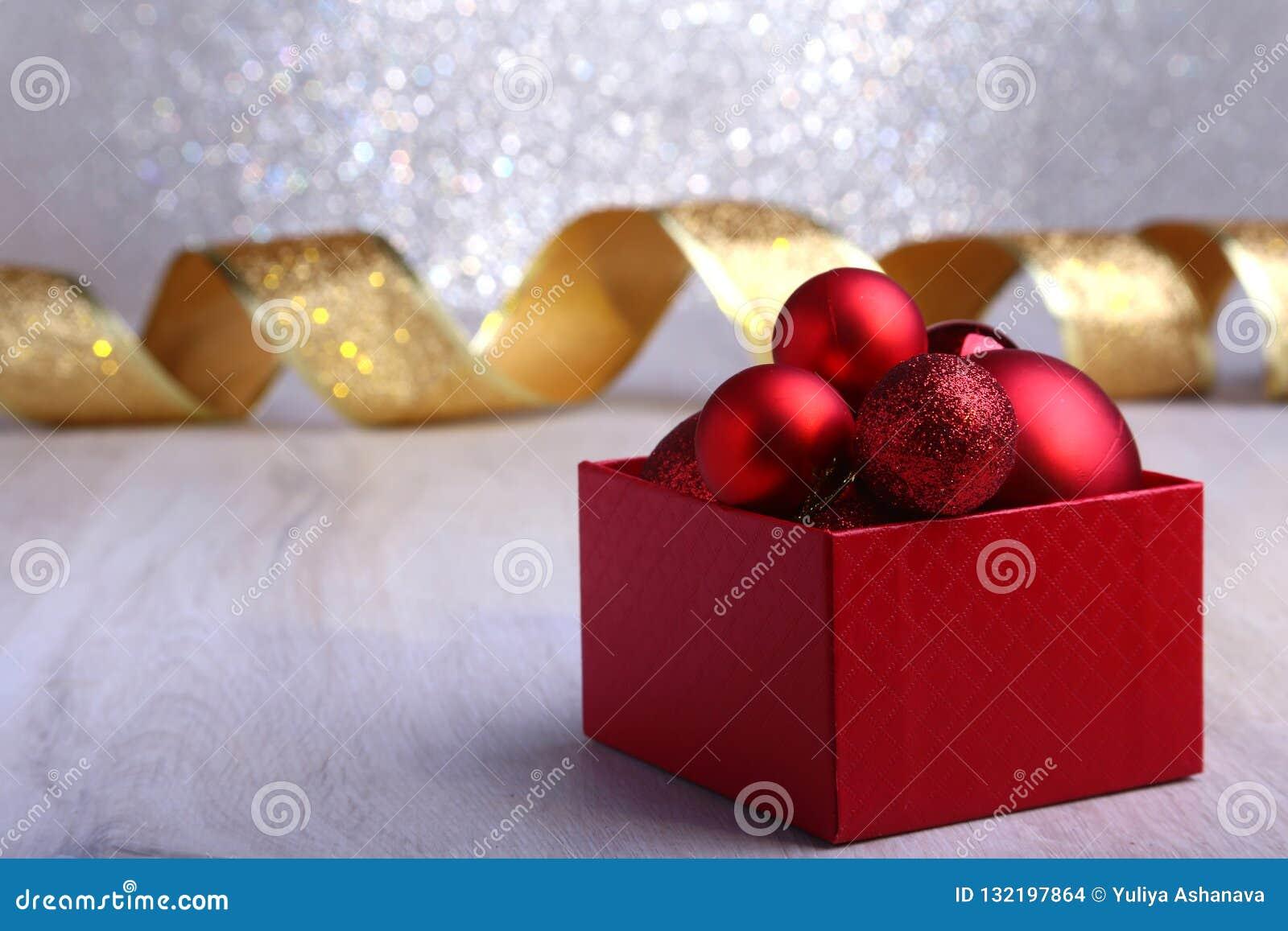 Presentes vermelhos coloridos com as bolas do Natal no fundo de prata