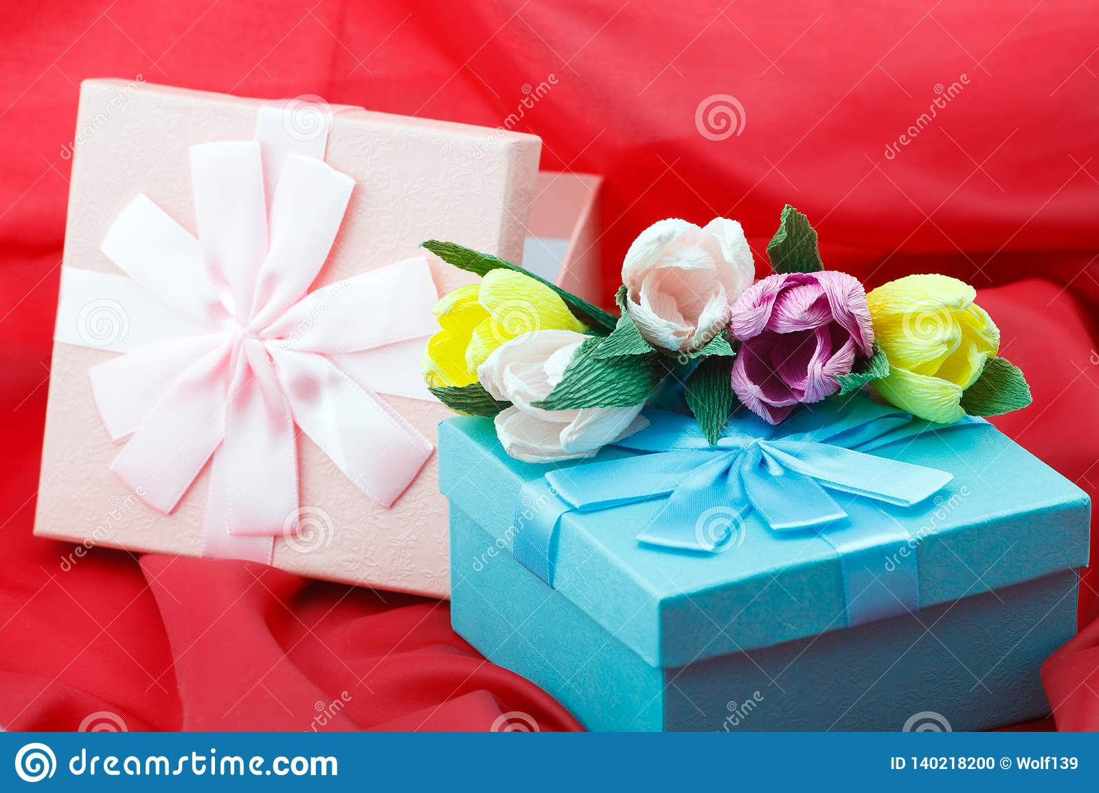 Presents In Boxes With Paper Flowers On The Red Background For
