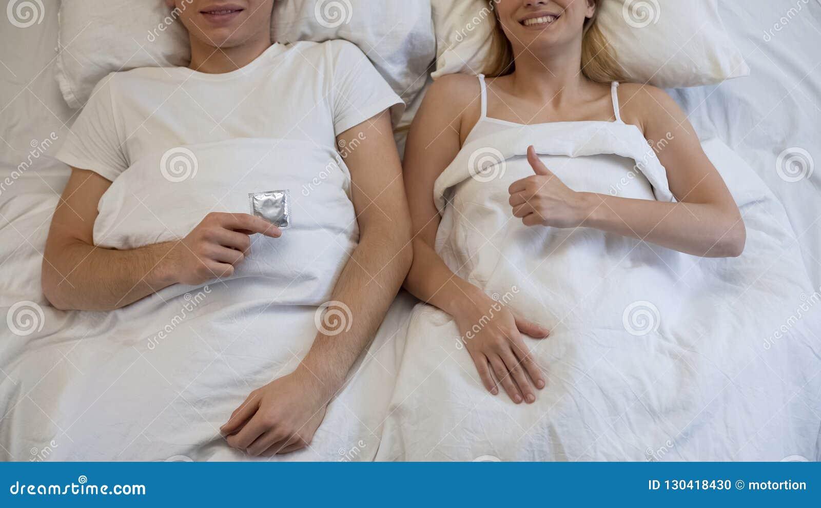 Preservativo e amiga da terra arrendada do homem que mostram os polegares acima, atitude responsável