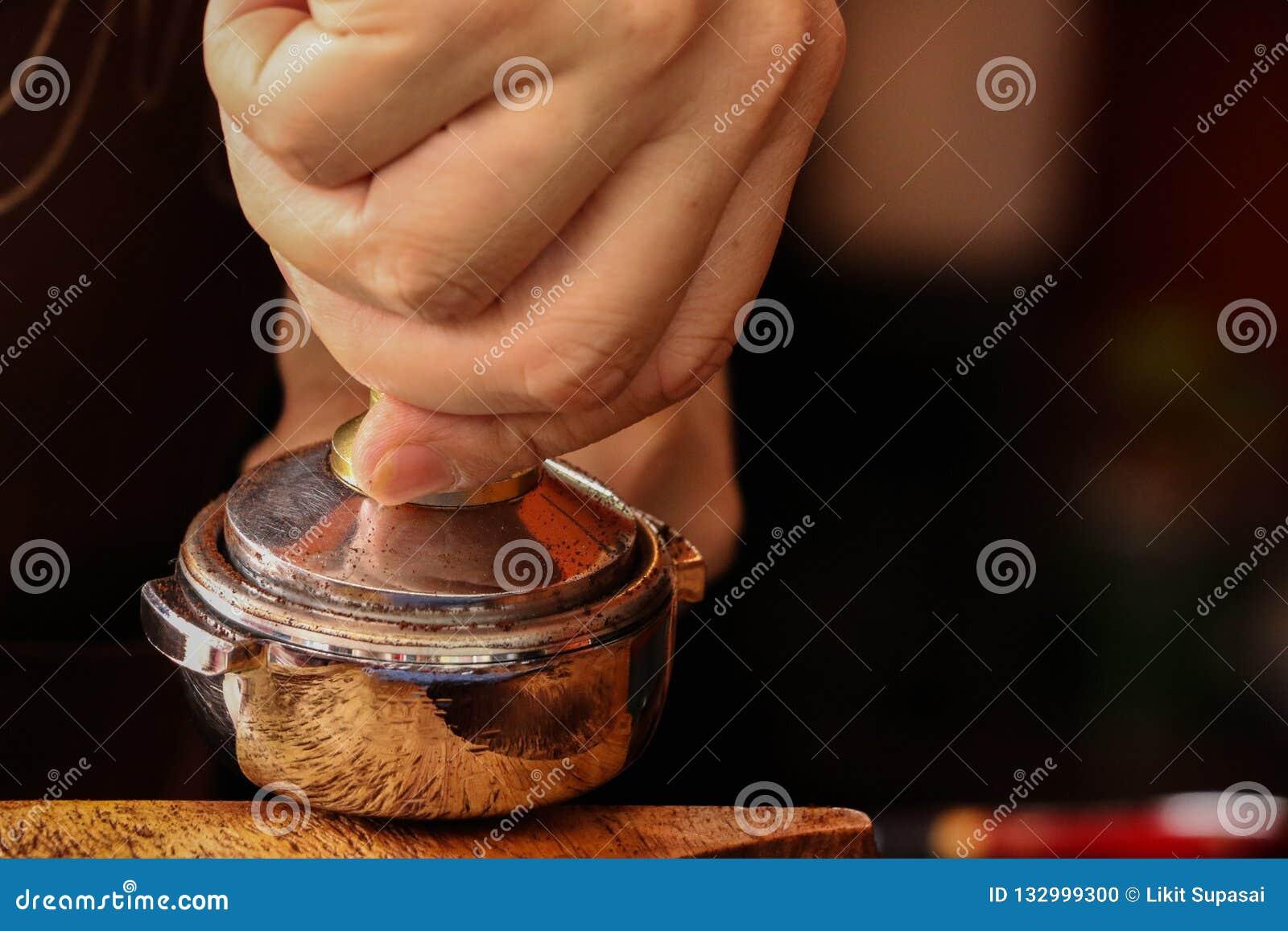 Presionar el café molido con el pisón