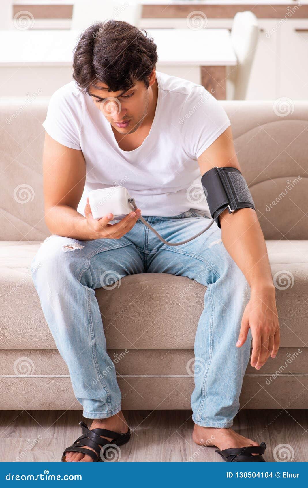 A pressão sanguínea de medição de homem novo em casa