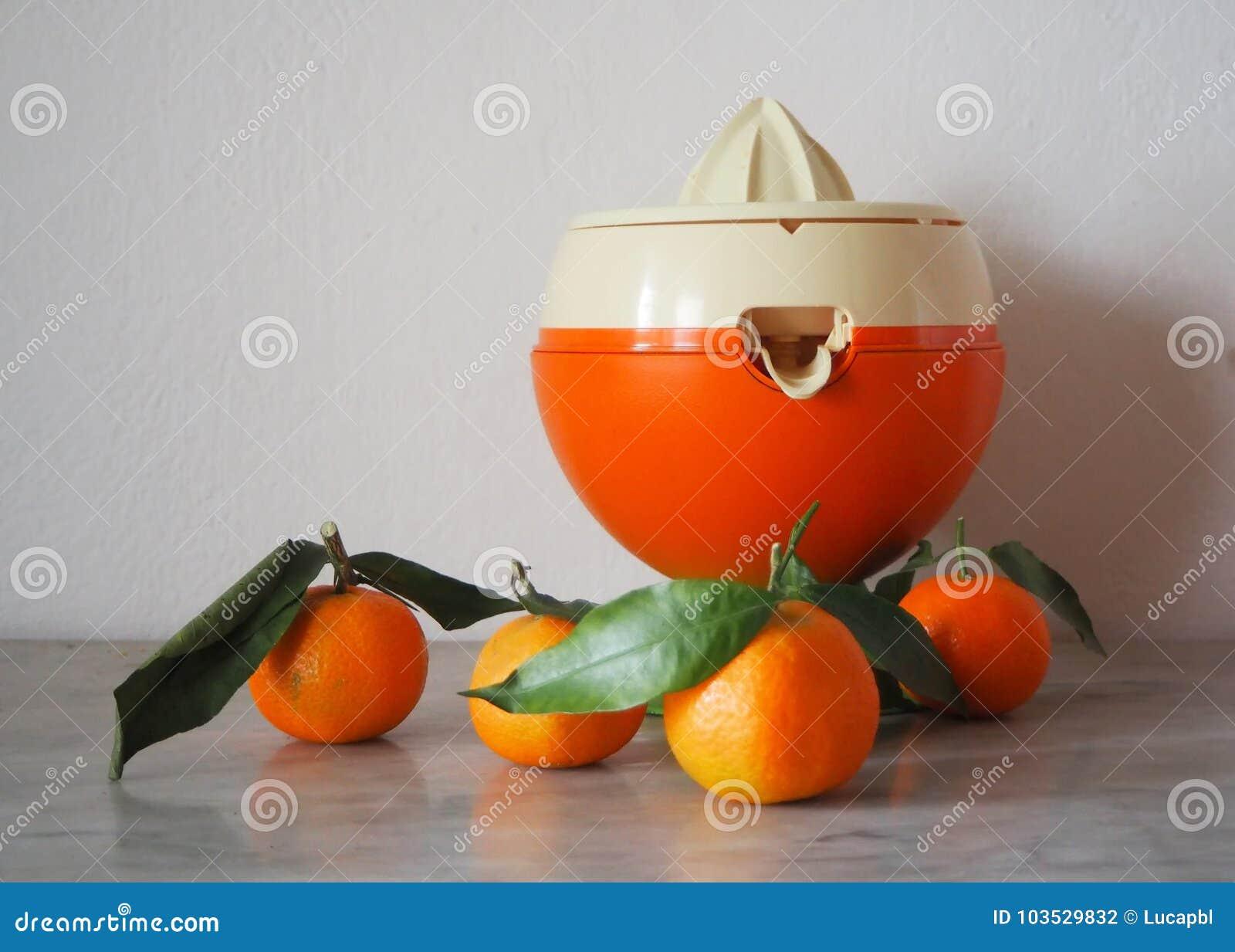 Presse-fruits orange et blanc avec quelques petites oranges sur une table de marbre