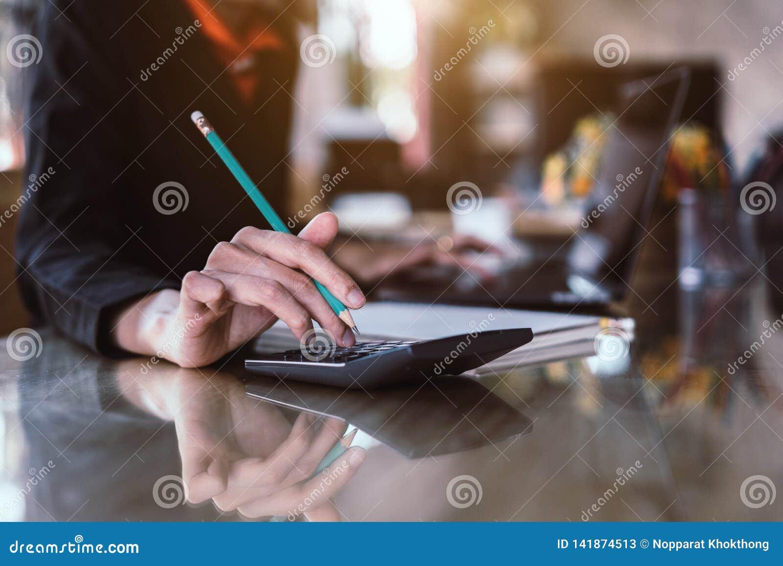 Pressing de main de femme d affaires sur la calculatrice pour l estimation de coût calculatrice