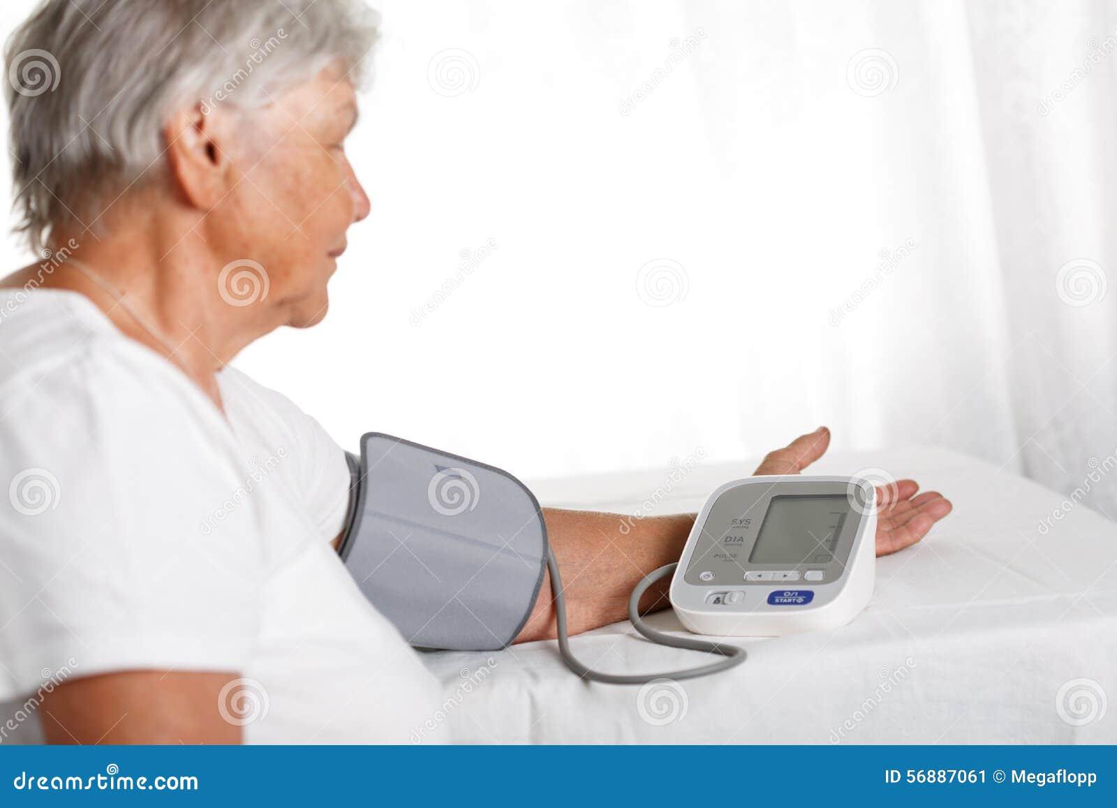 Pressione sanguigna di misurazione della donna più anziana con il manometro automatico a