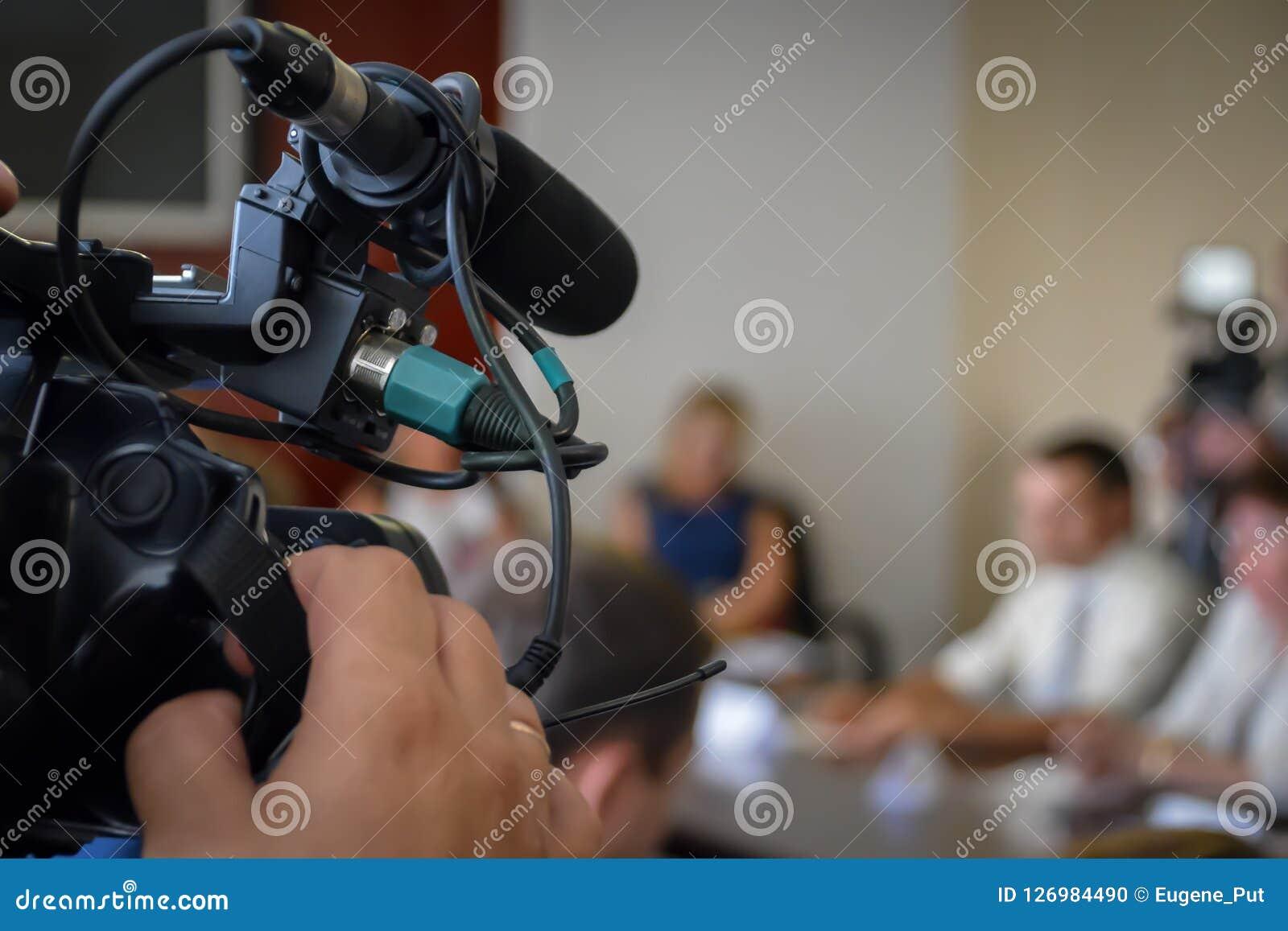 Presskonferens för inspelning för televisionkamera Talesmän på skrivbordet Journalister som täcker en presshändelse